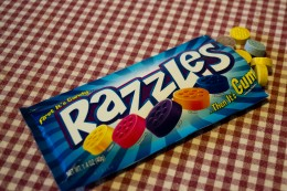 Razzles come in a blue packet with various flavor candies inside.