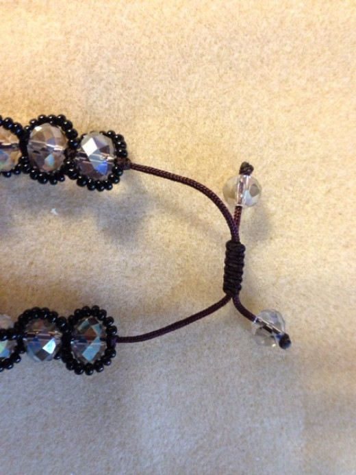 Make the bracelet large enough to fit your wrist.  Add the end beads, then tie and seal a knot after each end bead.