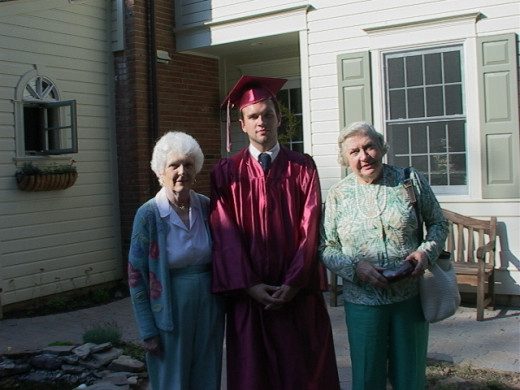 Posing with my grandmothers on my graduation day (next to the train village).