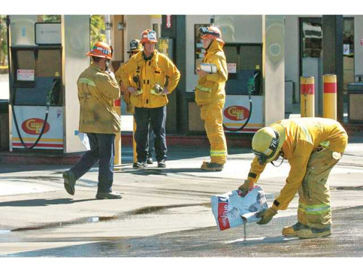 Firefighters using cat litter on gasoline.