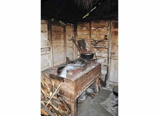 This kitchen is not located inside the house, but rather in a separate room.   The wooden structure has bricks which are heated by fire.   Meat is often smoked,.  Notice the black ceiling.