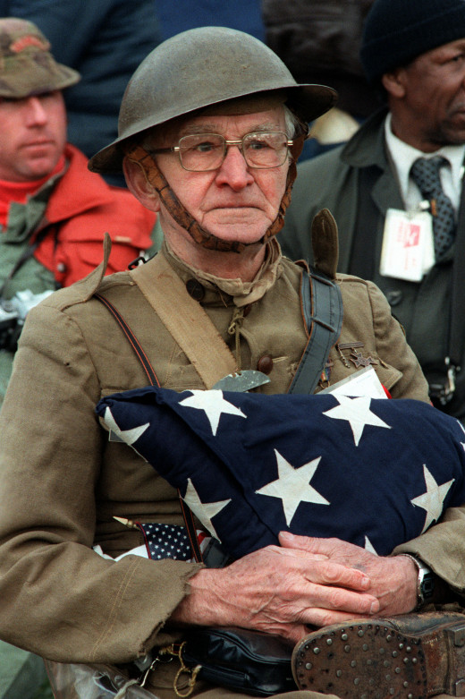 Joseph Ambrose, an 86-year-old World War I veteran, attends the dedication day parade for the Vietnam Veterans Memorial in 1982. He is holding the flag that covered the casket of his son, who was killed in the Korean War