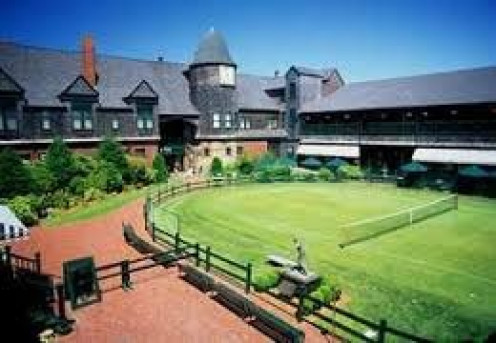 The entrance to The Tennis Hall of a Game has a walking track with a tennis court in the middle in the yards.