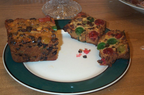 A slice of American fruitcake with cherries, nuts and candied fruit.