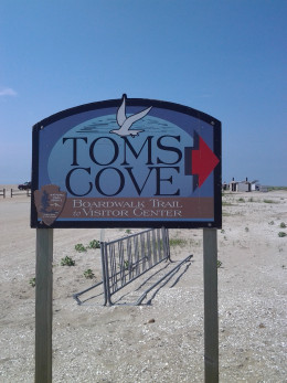 The colorful sign for the island's only public beach at Tom's Cove.