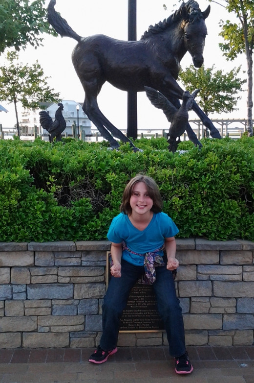My daughter in front of the statue of Misty, found on Main St. at the center of town.
