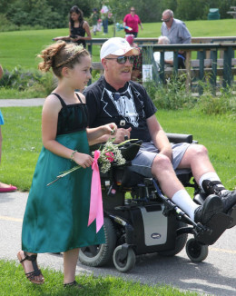 Little girl walking with a disabled man.