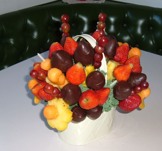 Create a fruit bouquet with skewers and a variety of individual and cut fruits.