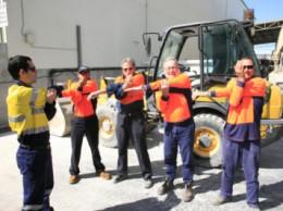 four men in orange work vests stretching