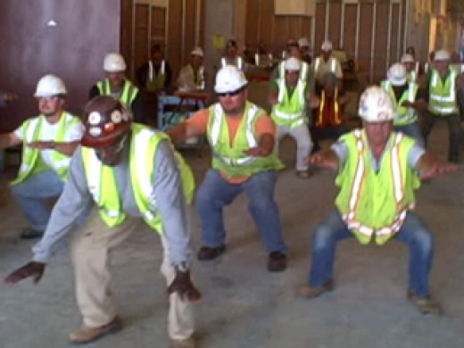 Group of Construction Workers in Green Safety Vests with Hard Hats Stretching