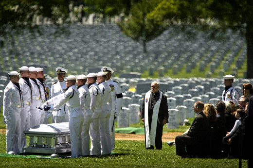 Members of the U.S. Navy Ceremonial Guard fold the American flag over the casket bearing the remains of sailors killed in the Vietnam War during a graveside interment ceremony at Arlington National Cemetery. Lt. Dennis Peterson, Ensign Donald Frye an