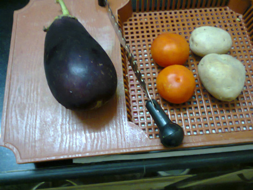 Brinjal, Tomato, Potato displayed in a vegetable cutter tray before cutting them