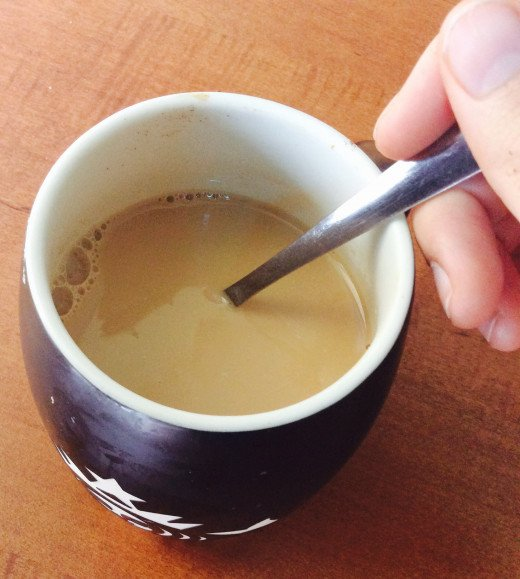 Milk, coffee, sugar, and creamer in cup, mixed