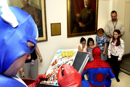 Marvel Comic action hero Captain America autographs a copy of the new armed forces comic book while Spiderman meets with children at the Pentagon in Washington, D.C