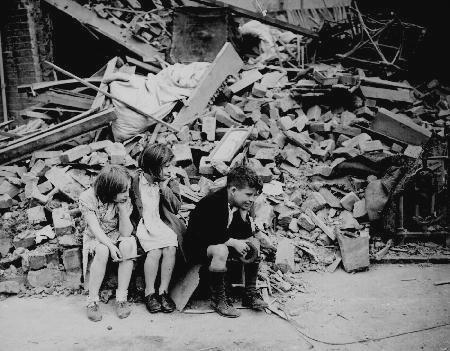 Children sitting outside a bombed-out building, London 1940.