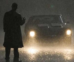 Rutger Hauer waits in the rain for an unsuspecting driver (C. Thomas Howell) to pick him up in The Hitcher
