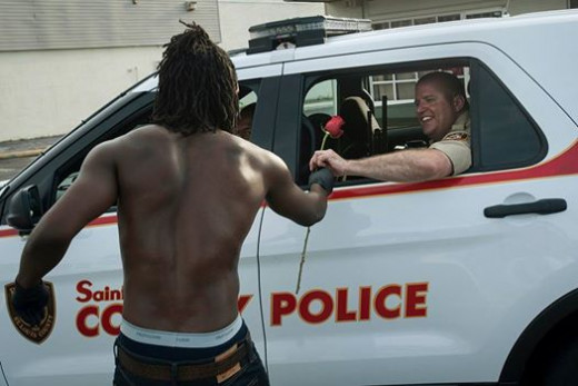 Resident hands police officer a rose in gratitude for helping clean streets and restore peace in Ferguson.