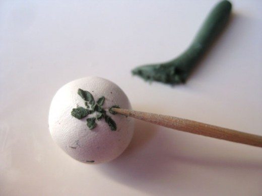 """Painting"" a shamrock onto the bead with the sharp end of a toothpick."