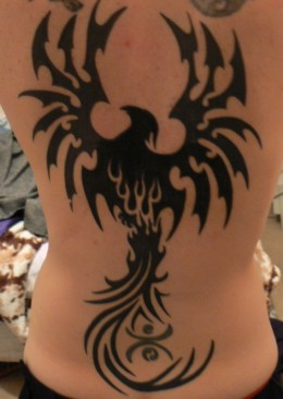 A full back Phoenix Tattoo that is well defined by the black ink.