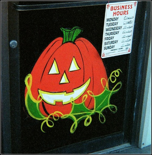 Halloween Pumpkin Painting: This delightful pumpkin greets customers on the bottom of a door frame.