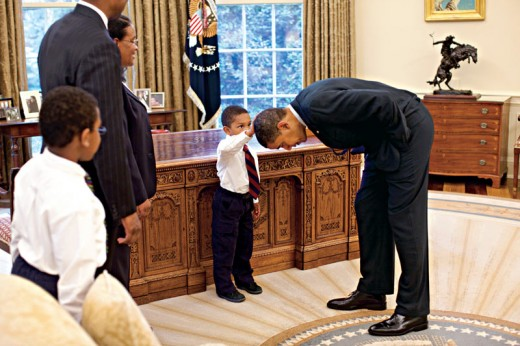 A young child touches President Obama's head during a family trip to the White.