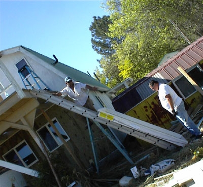 These are the men who plan to move the door up the ladder. Larry is on the top, Kosta on the bottom. Keep in mind that Kosta cannot bend over all the way to the bottom rung to give the door a push from the bottom.