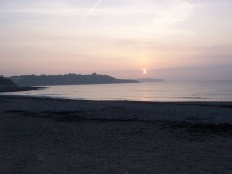 Looking out from Gyllyngvase Beach towards Pendennis Headland at dawn.
