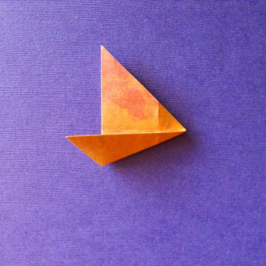 Unfold and refold as in(2). Bring the fold edge to the center as shown.