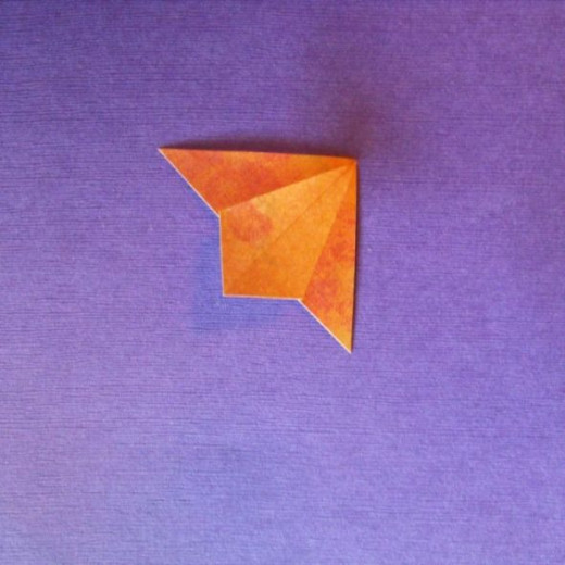 Unfold again and use the prefolds to make the squished triangle shown.