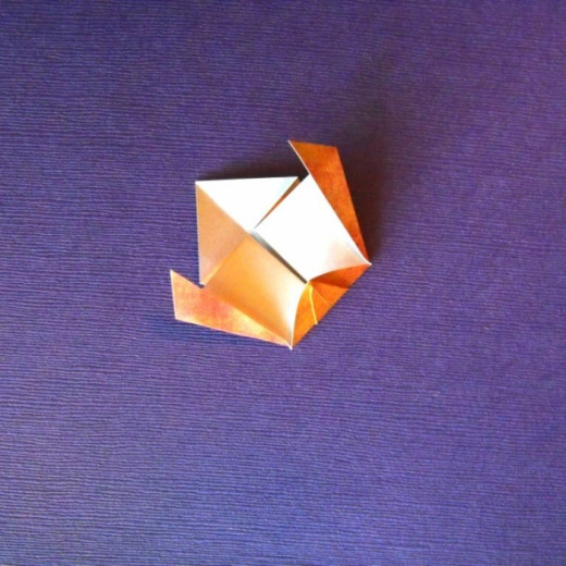 Turn over and fashion diagonal folds by folding outer points toward the center.