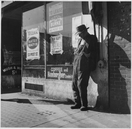 Depression, Unemployed,destitute man leaning against vacant store-photo by Dorothea Lange
