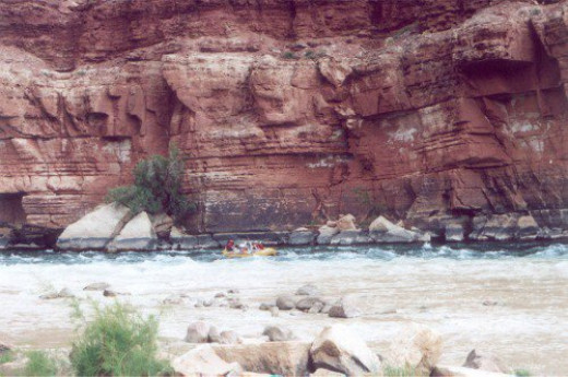 There is a yellow raft doing whitewater rafting close to the center, in the water. Glen Canyon.