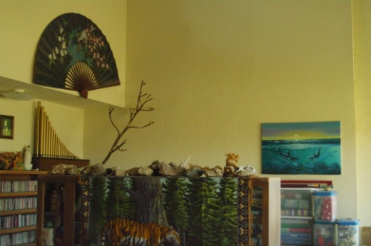 The corner of the room. Fan, dolphin painting, tiger tapestry.