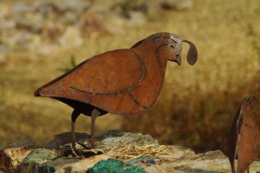 Gambel's Quail. Family of five quail sculptures on rock wall made from native Arizona rocks.