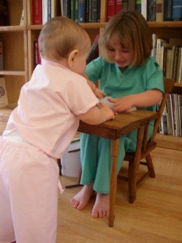Two children play wearing scrubs.