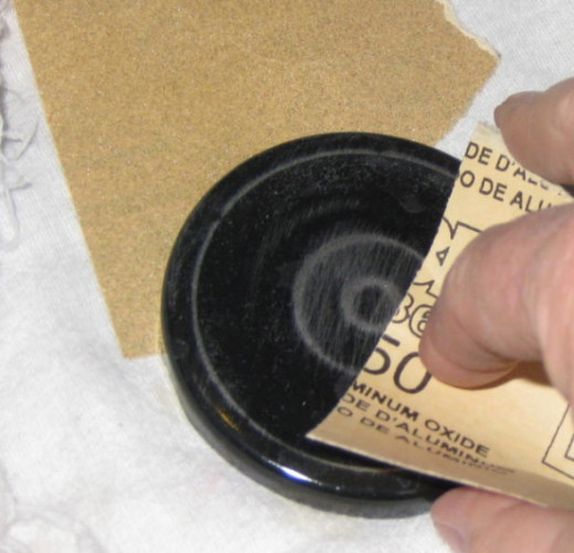 Sand the jar lids. If you're going to paint the entire jar lid, a quick sanding will rough up the surface to let the paint adhere better. Wipe off the dust with a damp rag or paper towel.