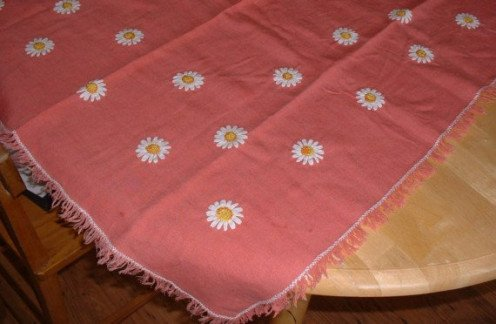 Vintage tablecloth with ribbon flowers and fringed edges.