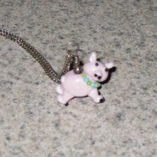 Pink pig wearing beads. A woman made this pig bead for me.