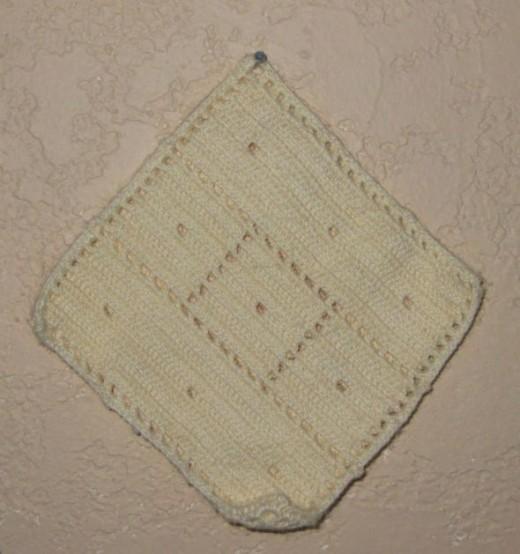 Knitted potholder in cream
