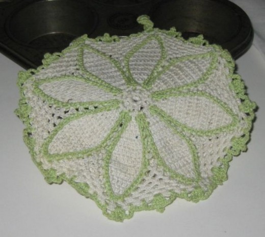 Crocheted potholder with white and green thread.