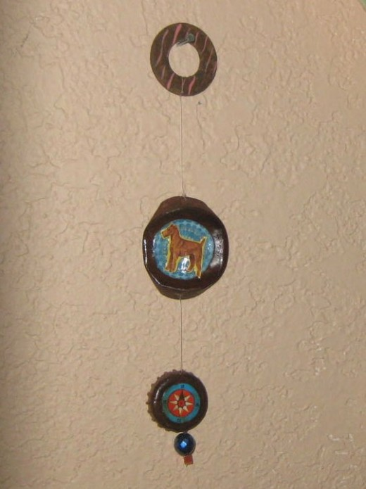 Wall hanging using a flattened tin lid, bottle cap, washer and beads and paper.