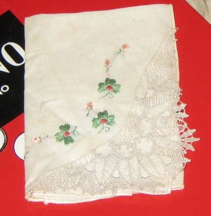Tiny green flowers embroidered on handkerchief with lace tatting at corner.