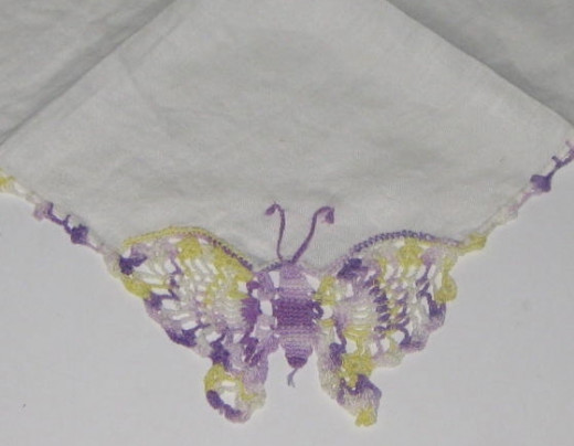 Butterfly embroidered on the corner of a white vintage hankie.
