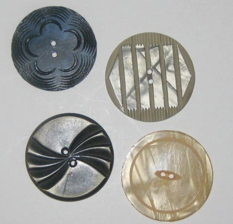 These large decorative sewing buttons are carved shell and plastic.