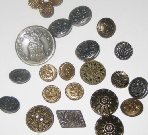 An assortment of metal buttons. All of these metal buttons are decorative and all but one has a shank at the back so all of the button's beauty shows.