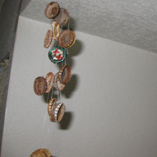 Punch holes in bottle caps to make a rustic wind chime. String illusion cord (clear fishing line works too!) to string them together.