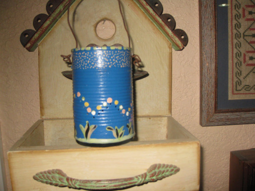 Painted tin can with handle and holes punched for the light to shine through.