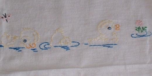 Embroidered ducks on tea towel.