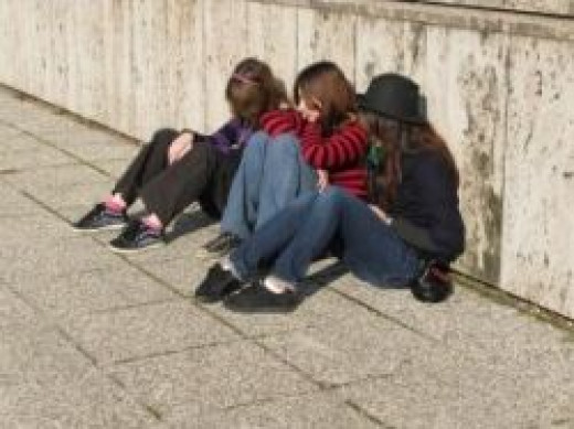 Three friends huddled together on the sidewalk in the cold