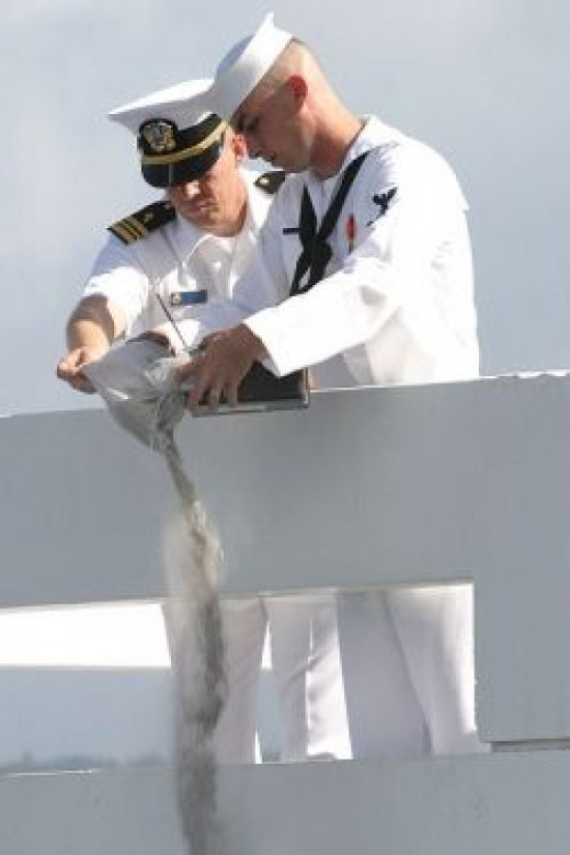 US Navy 030830-N-3228G-005 Cryptologic Technician Operator 3rd Class Evan Allen, assigned to the amphibious assault ship USS Peleliu (LHA 5) pours the cremated remains of his grandfather Darrell Allen, a Pearl Harbor survivor